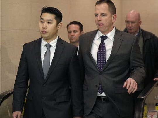 New York City police Officer Peter Liang, left, arrives at the courthouse for his arraignment on  Wednesday, Feb. 11, 2015, in New York. Liang, who fired into a darkened stairwell last November at a Brooklyn public housing complex, killed 28-year-old Akai Gurley and  was indicted by a grand jury in the shooting. He surrendered Wednesday to face criminal charges.