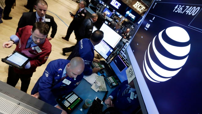 In this Monday, May 19, 2014, file photo, traders gather at the post that handles AT&T on the floor of the New York Stock Exchange. There are already a few online services that aim to replace cable, but they don't have many users yet. AT&T's DirecTV hopes to change that.