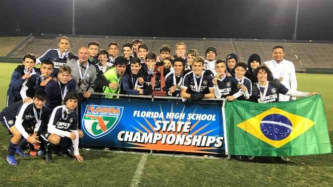 Members of the Boca Raton boys soccer team pose with the Class 7A state championship trophy. The Bobcats beat Orlando Boone 2-0 Saturday at Spec Martin Stadium in DeLand to complete a perfect 28-0 season.