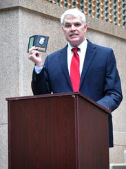 Assistant District Attorney John Gillespie holds the