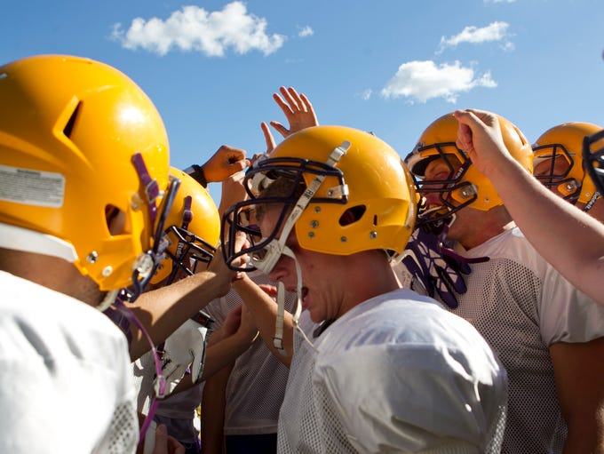 Players break it down in the huddle before practice at Pittsville High School, Tuesday, Aug. 12, 2014.