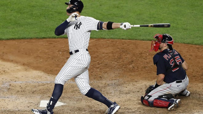 New York Yankees' Aaron Judge follows through on an eighth-inning, two-run home run against the Boston Red Sox in a baseball game Sunday, Aug. 2, 2020, at Yankee Stadium in New York. Red Sox catcher Kevin Plawecki is at right.