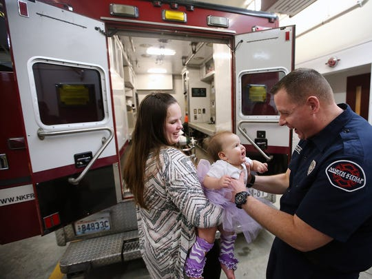 North Kitsap Fire and Rescue firefighter/paramedic Craig Barnard takes one-year-old Eleanor from her mom Lakeisha Rogers while they stand behind Medic 81 at  North Kitsap Fire & Rescue Headquarters Station 81 in Kingston on Tuesday, Feb. 6, 2018. Barnard delivered Eleanor a year earlier in the back of the medic unit, just before the intersection of SR 307 and SR 305, while transporting them from their Little Boston home to the hospital. The Rogers family stopped by the station to celebrate Eleanor's first birthday with the first responders who were there.