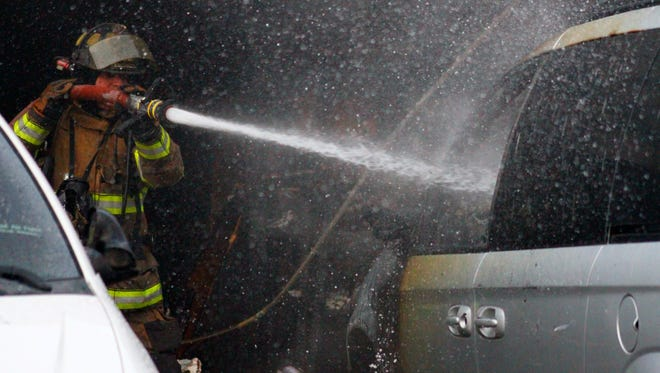 An Alamogordo Fire Department firefighter sprays down a minivan Wednesday evening. Emergency officials responded to a structure fire on the 3600 block of Fernwood.