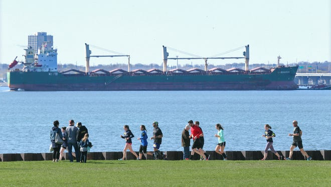 Runners fill the bike path on the lakefront as a ship makes its way into the Port of Milwaukee.