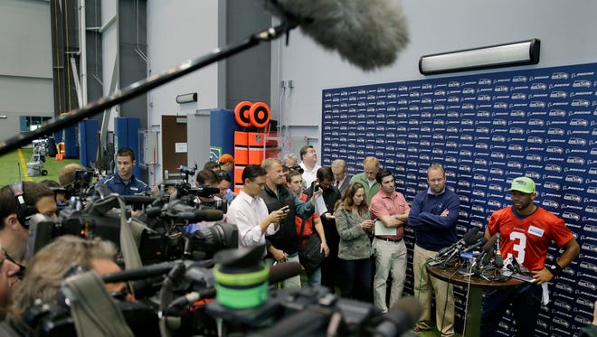 Seattle Seahawks quarterback Russell Wilson, right, listens to questions from reporters about his ongoing contract negotiations with the Seahawks following an organized team activity Tuesday, June 2, 2015, in Renton, Wash.