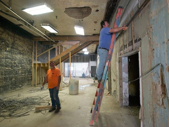 Scott Maloney, left, and Tim Price, right, works on demolishing the interior space of the former Consumer Credit Counseling Services of West Florida, building on Palafox Place. The building located at 14 Palafox Place is being turned into a cigar bar.