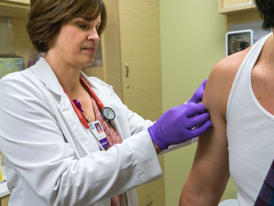 A patient receives a flu shot by a physician at a Sacred Heart Clinic at Walgreens on Dec. 29, 2017.
