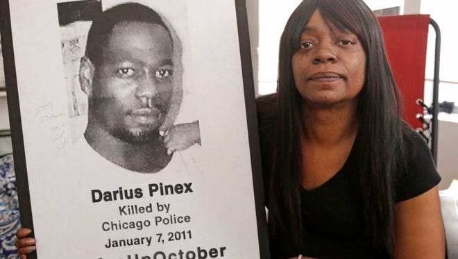 Gloria Pinex holds a photo of her son Darius Pinex, Thursday, Dec. 17, 2015, photo at her home in Chicago. Darius, was killed by Chicago police in 2011.