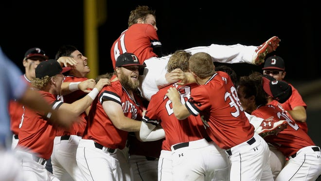 Davidson's Will Robertson (41) jumps onto teammates after the Wildcats defeated North Carolina 2-1 in an NCAA college baseball tournament regional game in Chapel Hill, N.C. on Sunday.