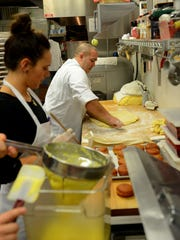 Owner and head chef Pete Counseller rolls out fresh dough for a new batch of packzi as pastry chef Katie Lambert, center, fills ones already cooked and Natalie Davenport prepares some made-from-scratch cream filling for the packzi early Feb. 9, 2016 at Glazed and Confused bakery in downtown Lansing.