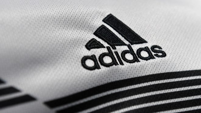 The Adidas company logo is on display during the company's annual press conference of Germany's sportgoods company Adidas in Herzogenaurach, southern Germany, on March 14, 2018.The company uses apps and other channels to sell directly to customers, rather than just offering its products in third party stores.