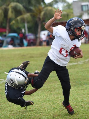 Outlaws player Zavier Camacho is grabbed by a Guam Raiders defender during their Guam National Youth Football Federation game at Eagles Field on Aug. 12, 2017.