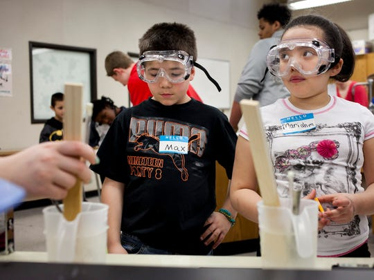 Crull Elementary third-graders Max Daniels, 9, and Mariahm Meadows, 8, wear safety goggles as they do an experiment testing heat retention in different materials during Science Day Friday, March 27 at Port Huron Northern High School.