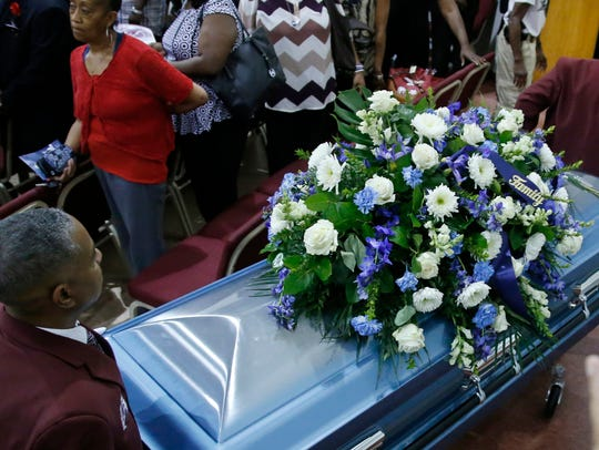 The casket of Terence Crutcher is wheeled out of the