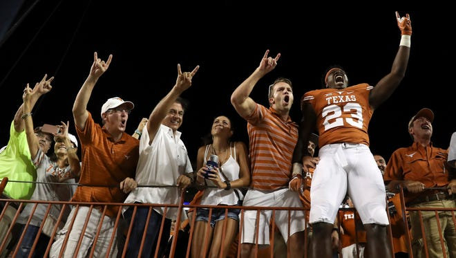Texas linebacker Jeffrey McCulloch (23) celebrates the Longhorns' victory with fans Sunday night.