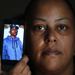 Rebecca O'Hara holds a phone showing a photo of her slain 25-year-old transgender son, Ashton O'Hara, in Detroit. Ashton O'Hara was found stabbed to death in a field in July.