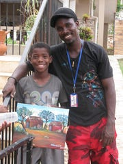 Gregory with a student he is mentoring at an orphange in Jacmel, Haiti. Gregory was born and raised in Port-au-Prince, Haiti and regularly travels back to his home country to teach art to children.