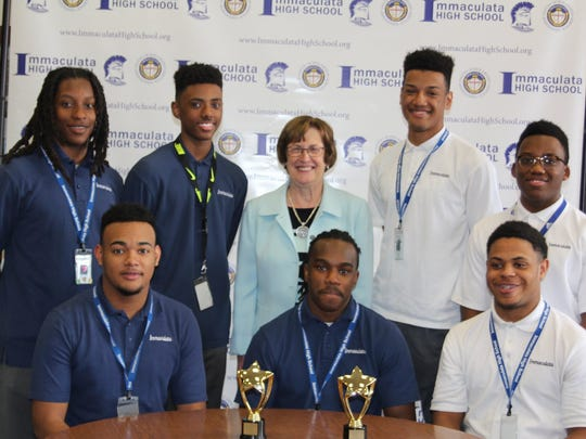Paul Robeson Youth Achievement Award winners from Immaculata, (pictured with Principal Jean Kline) include, seated from left to right,Xavier Powell,andShahkyle Matthews; and standing from left to right,Pelton Esannason, Jaden Honis, Austin Ralph-Charriez, and John Williams.