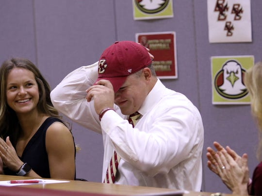 First Baptist Academy linebacker Joe Sparacio smiles as he puts on his Boston College hat after signing his National Letter of Intent during the Early Signing Period on Wednesday, Dec. 20, 2017.