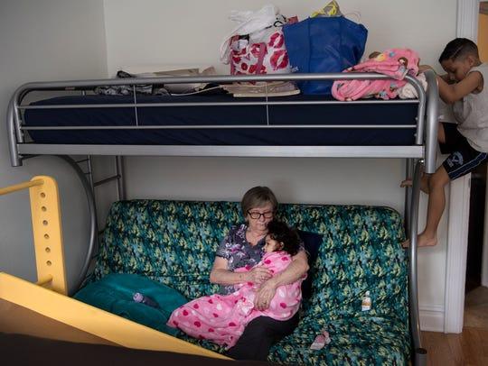 Lynne Stanley, una enfermera sostiene a Darah, 1, despues de una session de fisioterapia a la misma vez su hermano, Andre, baja de su cama en un cuarto en el departamento adonde vive Darah y su familia el viernes, 16 de marzo de 2018.