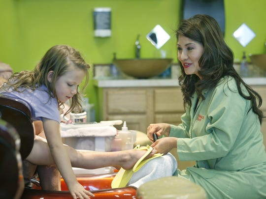 Morgan Murray, 5, of Penfield gets her nails done by Pro Nails owner Holly Phan Sackett in Penfield. Sackett also uses the site as a donation drop-off for local charities. She escaped Vietnam by boat.