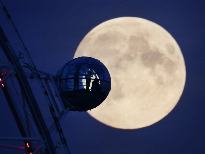 Visitors to The London Eye ferris wheel view the nearly full moon in Whitehall on Sept. 8, 2014, in London. This is the third supermoon this year, with it occurring in full Sept. 9.