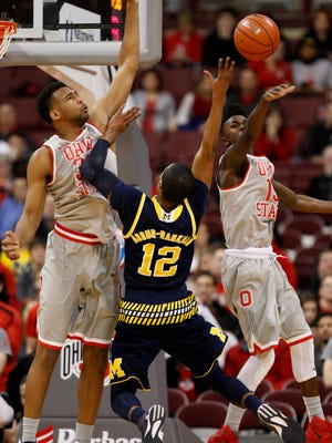 Ohio State's Kam Williams, right, blocks a shot by Michigan's Muhammad-Ali Abdur-Rahkman, center, as Ohio State's Trevor Thompson guards during the second half of an NCAA college basketball game in Columbus, Ohio, Tuesday, Feb. 16, 2016. Ohio State won 76-66.