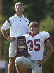 MICKEY WELSH/ADVERTISER FILE Trinity head football coach Randy Ragsdale and lineman Tommy Trott with the AHSAA Class 4A state championship trophy in 2004. Trinity head football coach Randy Ragsdale and lineman Tommy Trott with the AHSAA Class 4A state championship trophy on Monday August 2, 2004 at the school in Montgomery, Ala.  For High School Football Tab. (Montgomery Advertiser, Mickey Welsh)