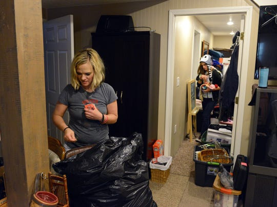 Stephanie Latier rummages through some of her belongings with her daughter, Emma, 12, at her parents' home in Zanesville. Most of the basement is filled with possessions from Stephanie and her daughters' old home.