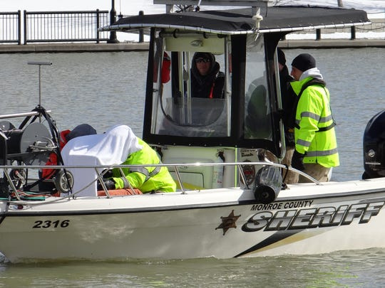 Scuba team members on a Monroe County Sheriff's boat shield  a sonar screen from the sun as they search the Genesee River Sunday.
