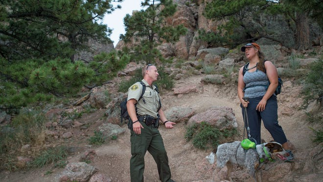 Larimer County Senior Ranger Zach Cook chats with Kalynn Morcom while she hikes with her dog, Coda, on the Horsetooth Rock Trail in Horsetooth Mountain Open Space on Friday, July 21, 2017.