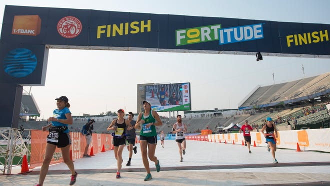 Runners cross the finish line at the CSU on-campus football stadium during the amateur race for the inaugural FORTitude 10K on Monday, September 4, 2017.