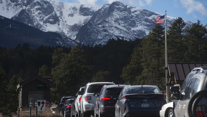 Cars line up at the Beaver Meadows entrance station to enter Rocky Mountain National Park on Friday, November 24, 2017.