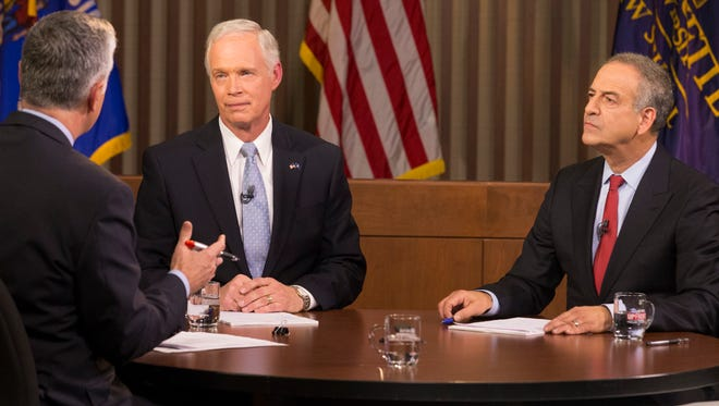 Republican U.S. Sen. Ron Johnson (center) and Democrat Russ Feingold (right) meet in their second and final debate Tuesday.