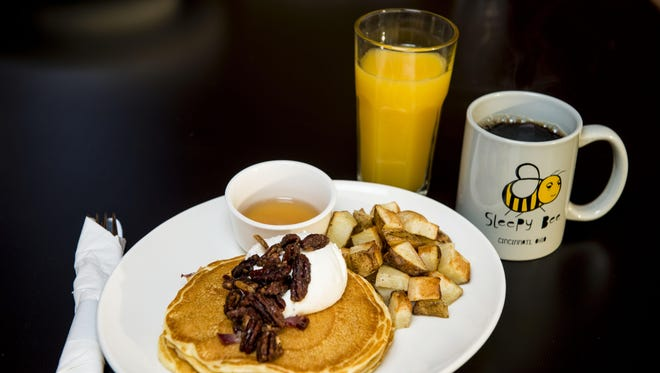 Piggy Cakes: buttermilk pancakes with bacon and maple syrup, topped with whipped cream and candied pecans and served with hash browns at the Oakley Sleepy Bee Cafe.