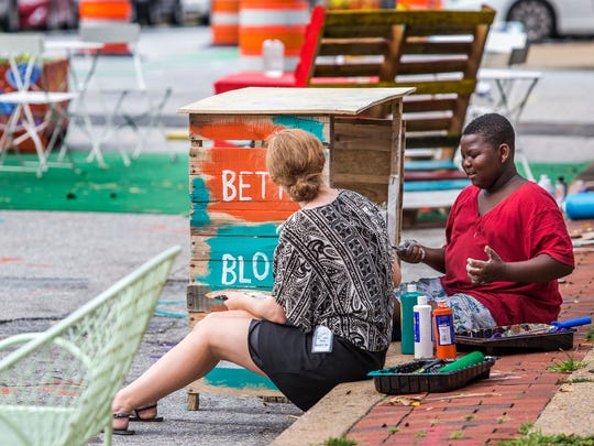Emma Cote (left) and Brenden Cephas, 10, paint a table along Union Street in Wilmington as part of the Better Block Project on Monday evening.