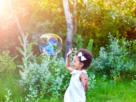 Happy little girl playing soap bubbles in park.