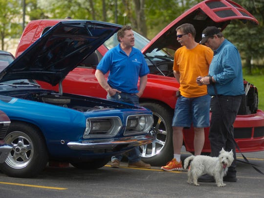 Rob Jones of Farmington Hills and Mark Olson of Livonia talk shop while standing around Farmington Hills resident Jim Wright's 1968 Plymouth Barracuda.