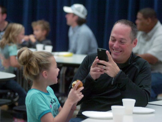"""Ryan Bell snaps a picture of his 9-year-old daughter, Sophie, during the """"Donuts with Dad"""" breakfast at Greenfield Elementary."""