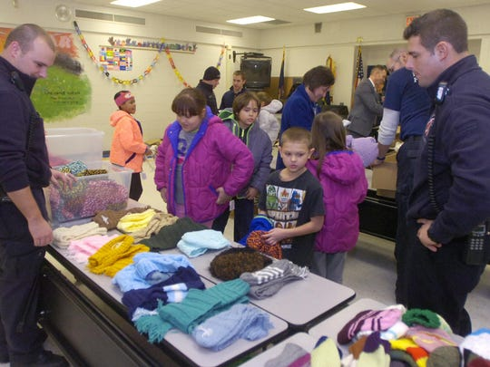 Farmington Hills firefighters raised $3,600 for Operation Warm, then brought an assortment of outerwear for Lanigan Elementary kids to take home.