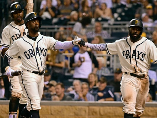 Pittsburgh Pirates' Andrew McCutchen, left, and Josh Harrison fist-bump after McCutchen's sacrifice fly scored Harrison in the eighth inning of a baseball game against the Cincinnati Reds in Pittsburgh, Friday, Sept. 9, 2016. (AP Photo/Fred Vuich)