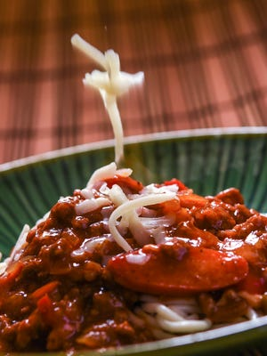 Grated cheese is added to a Filipino-style spaghetti prepared on March 21, 2017. The flavorful dish, tends to have a sweeter taste than the typical Italian-style sauce and is usually made with a ground beef/pork mix, sliced hot dogs, tomato sauce, banana ketchup and other ingredients.