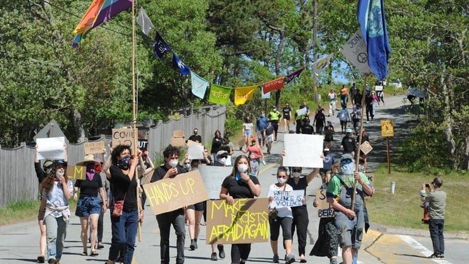 Demonstrators march along Lawrence Road to the Wellfleet police station Sunday.