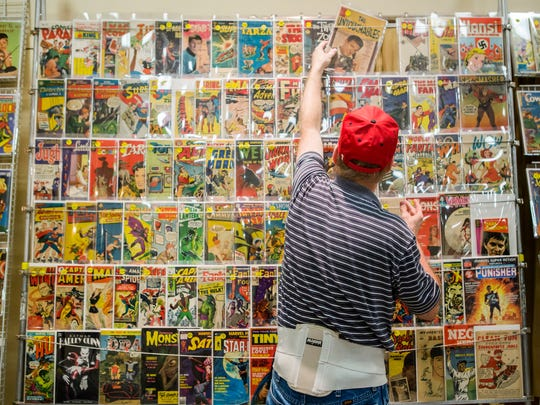 Gene Carpenter, from All-American Comics near Washington, D.C., sets comics on a display at his table at the First State Comic Con at the Mill Creek Fire Hall on Sunday afternoon.