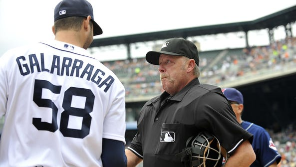 Umpire Jim Joyce shakes hands with Tigers pitcher Armando