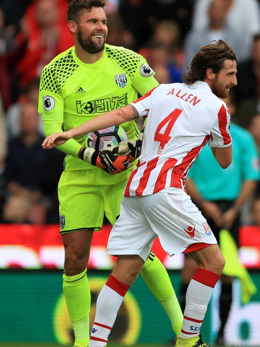 Stoke City's Joe Allen, right, and West Bromwich Albion goalkeeper Ben Foster during the English Premier League soccer match between Stoke City and West Bromwich Albion at the Bet365 Stadium in Stoke, England. Saturday, Sept, 24. (Tim Goode/PA via AP)