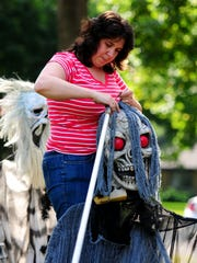 Julia Hansen puts up Halloween decorations at her home in Green Bay last month.