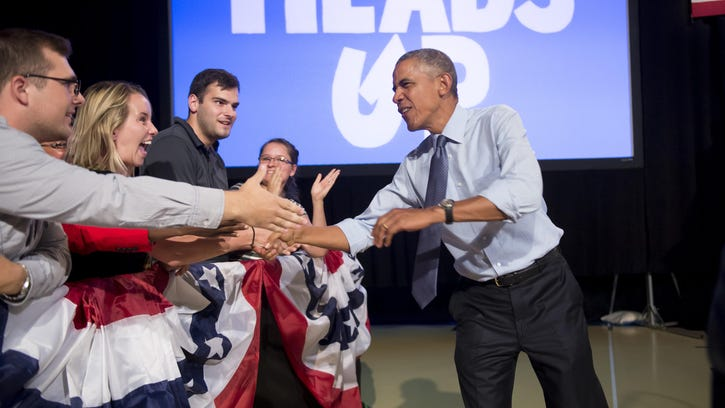 President Barack Obama shakes hands as he walks on stage to give a speech at Macomb Community College on Sept. 9, 2015.