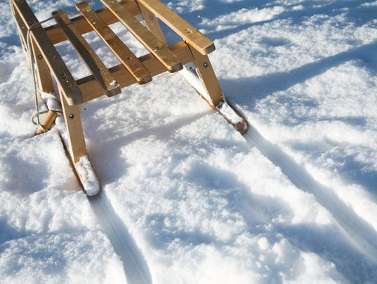 Wooden sled on white snow with tracks left behind in winter